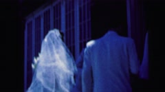 1964: groom ushers bride into building after bridal party enters CAMDEN Stock Footage
