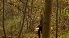 Beautiful slender girl walking in autumn forest holding a picnic basket. Profile Stock Footage