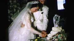 1964: a bride and groom embraced as they begin cutting the wedding cake CAMDEN Stock Footage