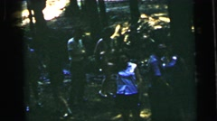 1964: dozens of people standing outdoor in a wooded area  Stock Footage