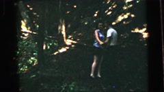 1964: a young couple walking and frolicking happily in a wooded area CAMDEN Stock Footage