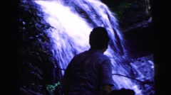 1964: a man is exploring the side of a waterfall trail accompanied by two ladies Stock Footage