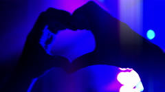 4K Woman Hands in Shape of Heart, Silhouette with Purple Stage Lights Background Stock Footage