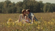 Cheerful family having fun outdoors in summer field Stock Footage