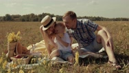 Young cheerful family in green field having little family picnic Stock Footage