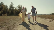 Sunny family walking along countryside road Stock Footage