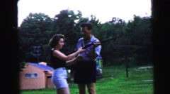1964: a man outdoors teaching a young woman how to fire a gun CAMDEN, NEW JERSEY Stock Footage