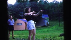 1964: a woman is shooting with a rifle while is being observed by a man CAMDEN Stock Footage