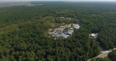 Aerial view of the meat factory through green forest. Stock Footage