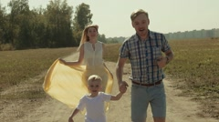 Beautiful family running in a field. Young father holding their son is hand Stock Footage