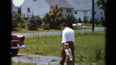1964: a father holds his boy's hand and walks him to a car in the driveway Stock Footage