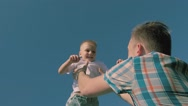 Close-up of young fair-skinned father throwing his son in the air Stock Footage