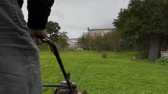Worker starting cut the grass in rainy day Stock Footage