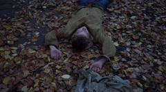 Post-apocalyptic world. Wanderer young boy with a backpack lying on the ground. Stock Footage
