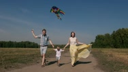 Joyful family flying a kite and running on the road with it Stock Footage