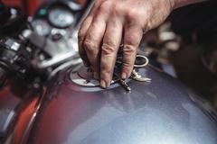 Mechanic closing a fuel tank of motor bike Stock Photos