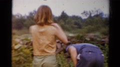 1964: three boys and a girl are picking wildflowers randomly by a wilderness Stock Footage