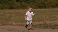 Cute child running and flying the kite. He smiles with flare Stock Footage