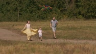 Family running together around the field flying a kite Stock Footage