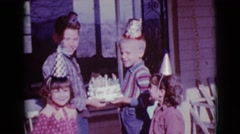 1968: two boys are holding a birthday cake with candles on the front porch  Stock Footage