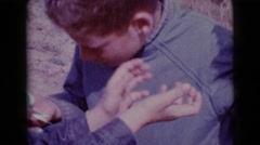 1968: a cute young boy outdoors, looking for easter eggs in the bush Stock Footage