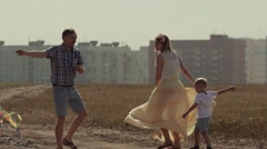 Family flying a kite together. Father shows his son how he can rotate the kite Stock Footage