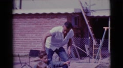 1968: a father playing with his two sons outdoor CLARKSDALE, ARIZONA Stock Footage