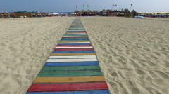 Walking pov on the colorful wooden walkway on sea beach sand. 4k steadicam Stock Footage