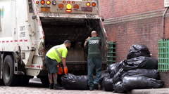 Two men loading trash into garbage truck in New York 4k Stock Footage