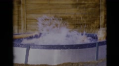 1968: two children playing splashing strongly on a portable pool CLARKSDALE Stock Footage