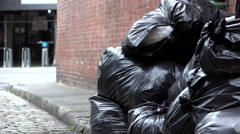 Trash bags in side street establishing shot of city 4k Stock Footage