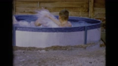 1968: two rambunctious boys wrestling and playing in a small swimming pool Stock Footage
