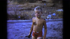 1968: a cute little boy outdoor in the yard playing in the mud CLARKSDALE Stock Footage