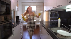 Happy housewife washing the dishes and dancing in the kitchen. Slow Motion. Stock Footage