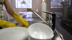 The housewife washes the dishes in the sink in the kitchen. Dolly shot. Stock Footage