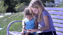 Girls sitting on park bench watching video on cell phone 4k Stock Footage