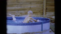 1968: a blonde haired and dark boy boy play around in a children swimming pool Stock Footage