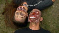 A pair of lovers zombie lie on the ground face to face, Halloween Stock Footage
