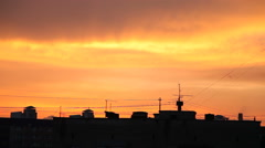 Sunset in town. Fluffy colorful clouds over black contour of buildings Stock Footage