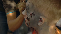 Make-up artist with a brush transforms man into a zombie, make-up for zombies Stock Footage