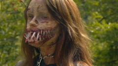 Zombie girl with sharp teeth and a good eye on the background of green trees Stock Footage