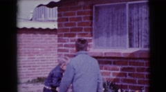 1968: two kids searching for easter eggs outdoor of their house CLARKSDALE Stock Footage