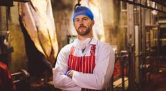 Portrait of butcher standing with arms crossed in meat storage room Stock Photos