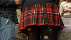 Girl in school plaid skirt and tattered black nylon tights Stock Footage