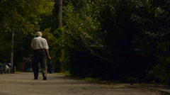 An elderly man walking along the road in a public park with a package Stock Footage