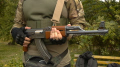 Person standing with a gun in his hand, close-up Stock Footage