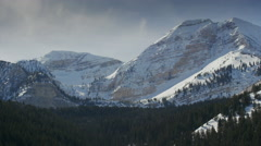 Wide panning shot of snow on mountain range / American Fork Canyon, Utah, United Stock Footage