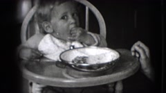 1942: toddler in a highchair eats lunch from a bowl with her hands. NEW YORK Stock Footage