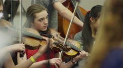 Medium shot of teenage girls playing violins in orchestra practice / American Stock Footage