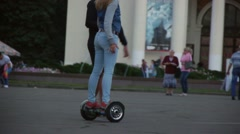 Girl learning to drive on electric scooter in the middle of a busy street Stock Footage